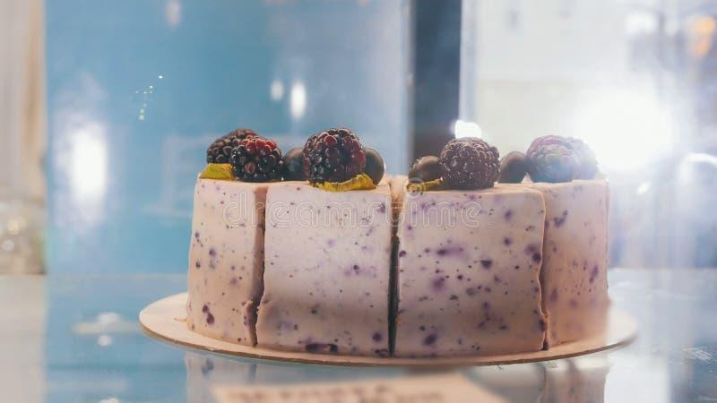 Ένα όμορφο κέικ βατόμουρων πίσω από την προθήκη στοκ εικόνα