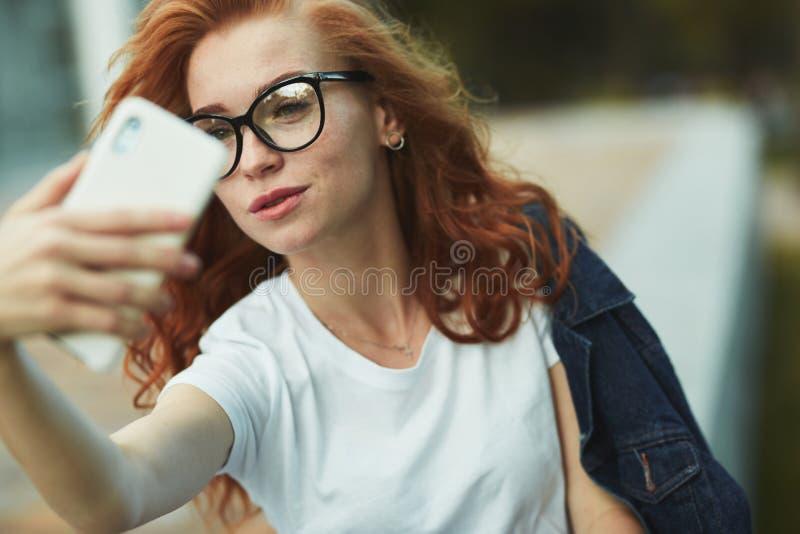Ένα όμορφο κοκκινομάλλες κορίτσι στηρίζεται σε έναν δημόσιο κήπο και παίρνει ένα selfie στο κινητό τηλέφωνό της Το κορίτσι φορά μ στοκ εικόνα με δικαίωμα ελεύθερης χρήσης