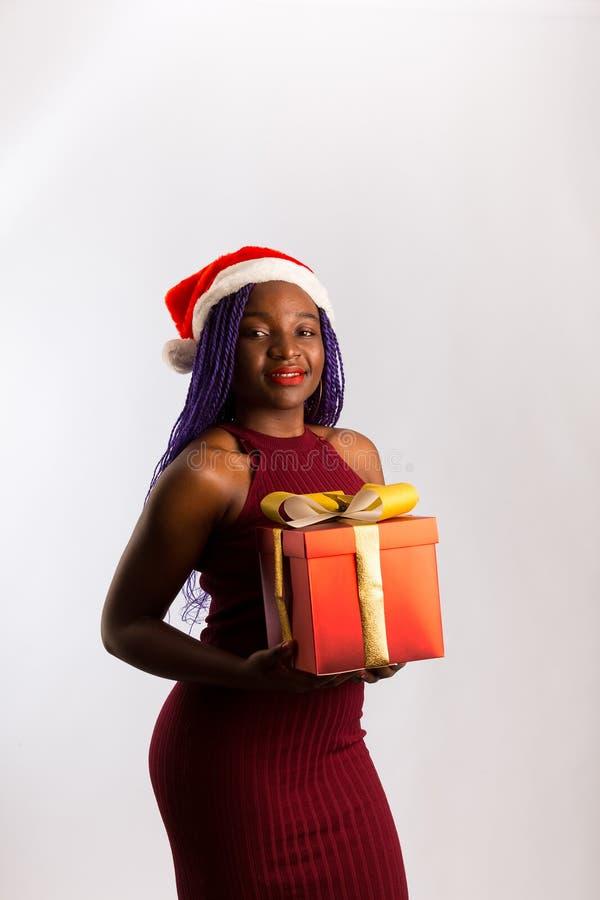 Ένα όμορφο κορίτσι από την Αφρο-Αμερική ντυμένο και ο Άγιος Βασίλης κρατά δώρα, κοιτώντας την κάμερα και χαμογελώντας, απομονωμέν στοκ φωτογραφίες με δικαίωμα ελεύθερης χρήσης