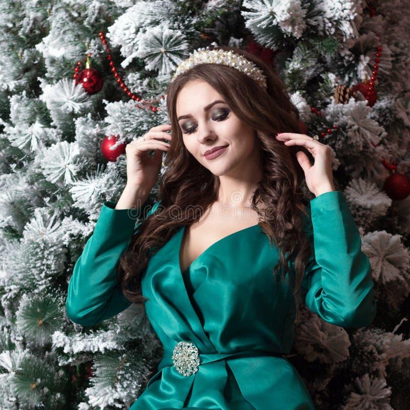 Ένα όμορφο κορίτσι με μακρυμάλλη σε ένα πράσινο φόρεμα με άσπρο diadem στο κεφάλι της κοντά στο χριστουγεννιάτικο δέντρο Μια τετρ στοκ εικόνες