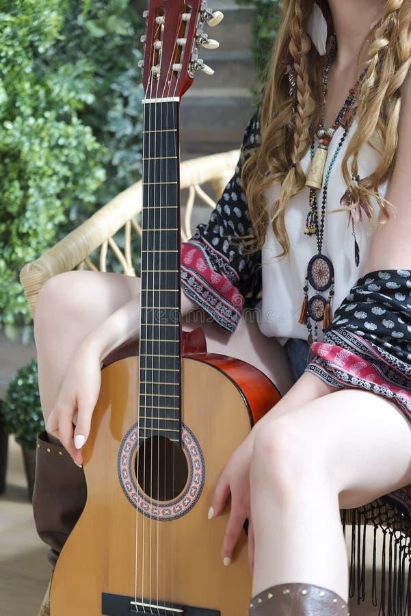 Ένα όμορφο κορίτσι με την κόκκινη σγουρή τρίχα κάθεται σε μια καρέκλα με μια κιθάρα επτά-σειράς στοκ φωτογραφίες με δικαίωμα ελεύθερης χρήσης