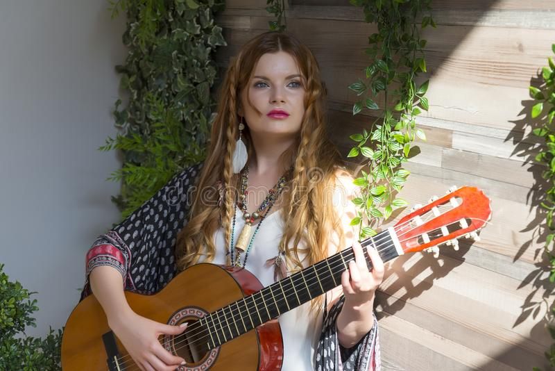 Ένα όμορφο κορίτσι με την κόκκινη σγουρή τρίχα στέκεται και κρατά μια κιθάρα επτά-σειράς στα χέρια της στοκ φωτογραφία
