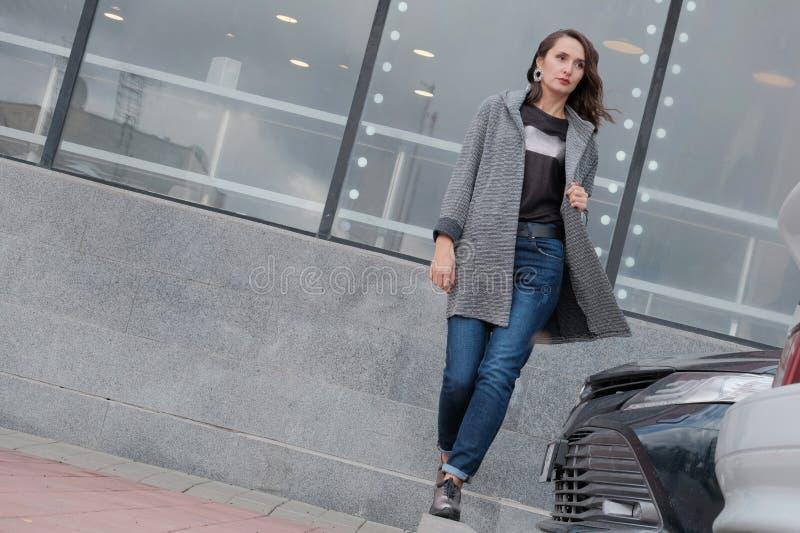 Ένα όμορφο κορίτσι περπατά μέσω της πόλης μετά από έναν χώρο στάθμευσης δίπλα σε ένα εμπορικό κέντρο Brunette σε ένα παλτό και πε στοκ εικόνες
