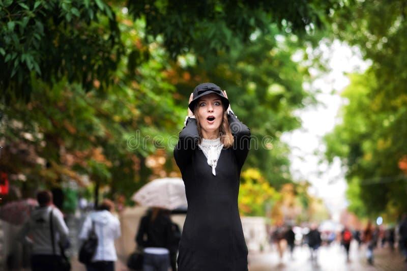 Ένα όμορφο κορίτσι σε ένα φωτεινό πολύχρωμο παλτό στο βροχερό καιρό στοκ εικόνες