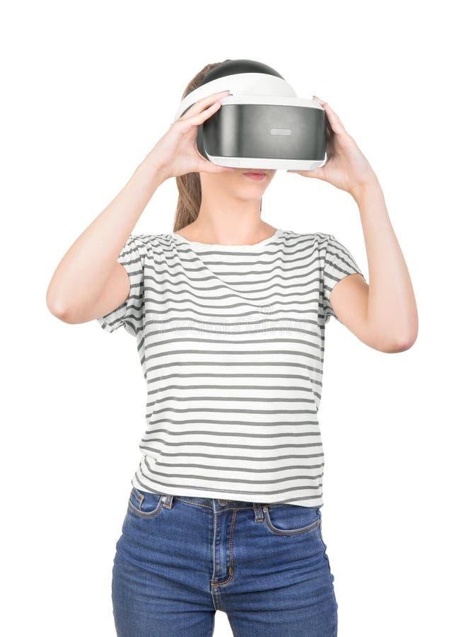 Ένα όμορφο κορίτσι στην κάσκα VR που απομονώνεται σε ένα άσπρο υπόβαθρο καινοτόμες τεχνολογίε&si Ένας θηλυκός gamer στα γυαλιά μι στοκ εικόνα με δικαίωμα ελεύθερης χρήσης