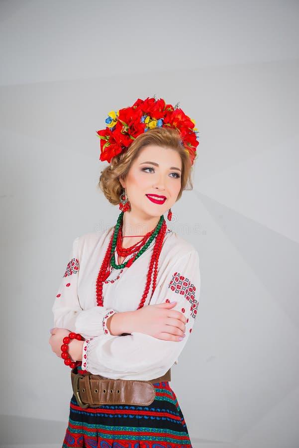 Ένα όμορφο κορίτσι στο εθνικό ουκρανικό κοστούμι Συλλήφθείτε στο στούντιο Κεντητική και σακάκι στεφάνι Κυκλίσκος των λουλουδιών χ στοκ φωτογραφία με δικαίωμα ελεύθερης χρήσης