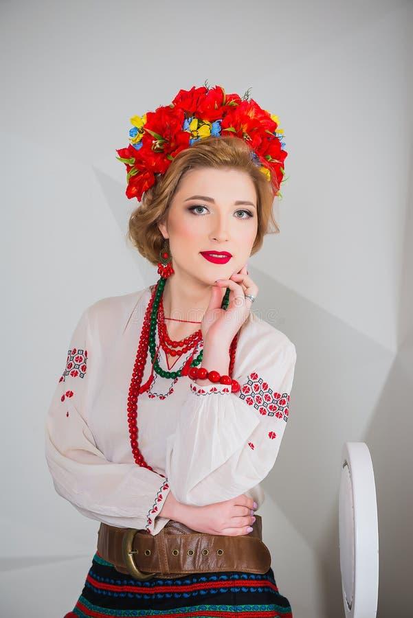 Ένα όμορφο κορίτσι στο εθνικό ουκρανικό κοστούμι Συλλήφθείτε στο στούντιο Κεντητική και σακάκι στεφάνι Κυκλίσκος των λουλουδιών χ στοκ εικόνα με δικαίωμα ελεύθερης χρήσης