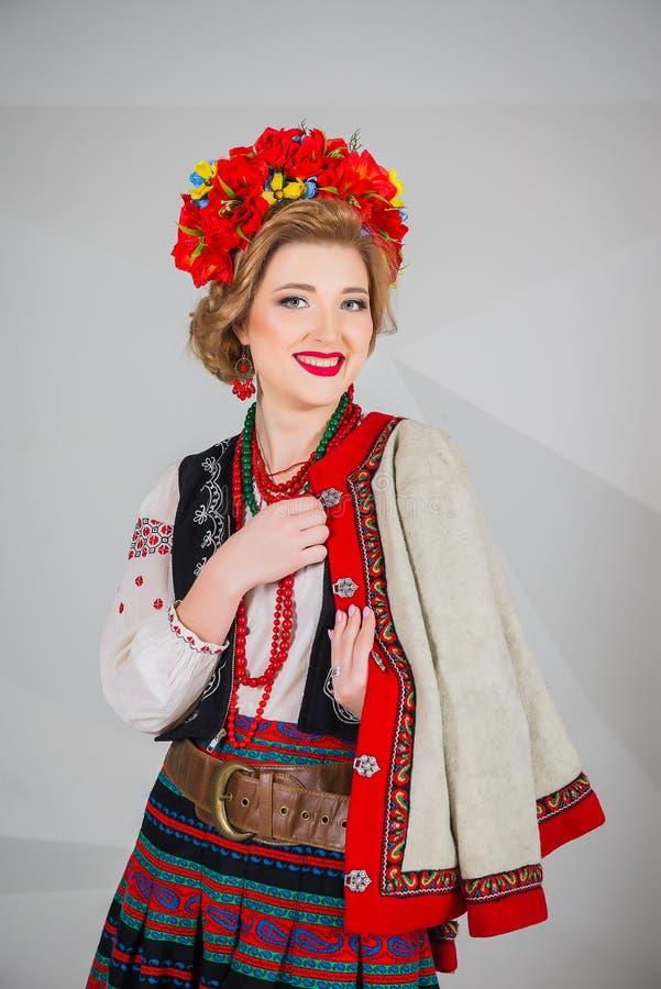 Ένα όμορφο κορίτσι στο εθνικό ουκρανικό κοστούμι Συλλήφθείτε στο στούντιο Κεντητική και σακάκι στεφάνι Κυκλίσκος των λουλουδιών χ στοκ εικόνες
