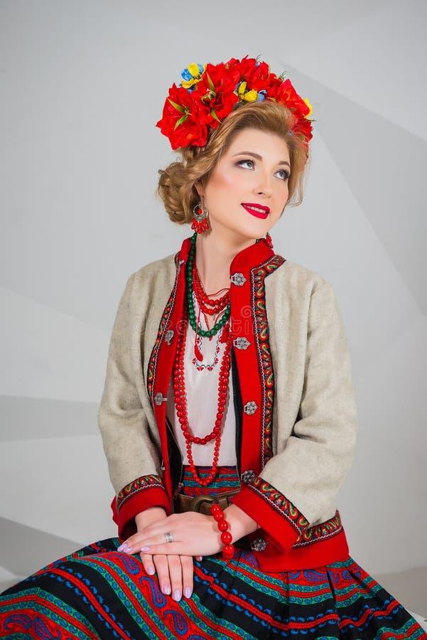 Ένα όμορφο κορίτσι στο εθνικό ουκρανικό κοστούμι Συλλήφθείτε στο στούντιο Κεντητική και σακάκι στεφάνι Κυκλίσκος των λουλουδιών χ στοκ εικόνα
