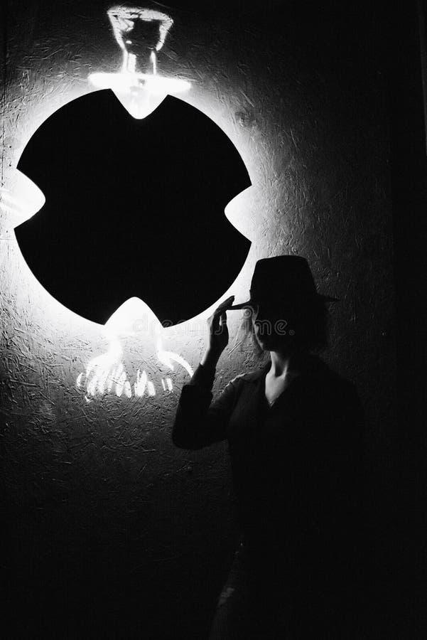 Ένα όμορφο κορίτσι brunette σε ένα μαύρο φόρεμα καπνίζει ένα hookah και αφήνει έξω τον καπνό στοκ φωτογραφίες