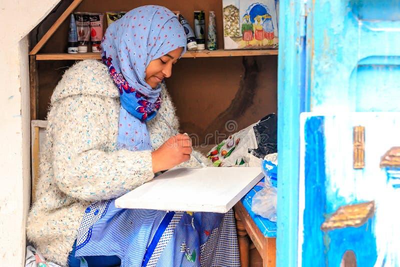 Ένα όμορφο μαροκινό κορίτσι, ένας μουσουλμάνος, καλλιτέχνης οδών χρωματίζει μια εικόνα με μια βούρτσα σε ένα μικρό εργαστήριο στοκ εικόνα με δικαίωμα ελεύθερης χρήσης