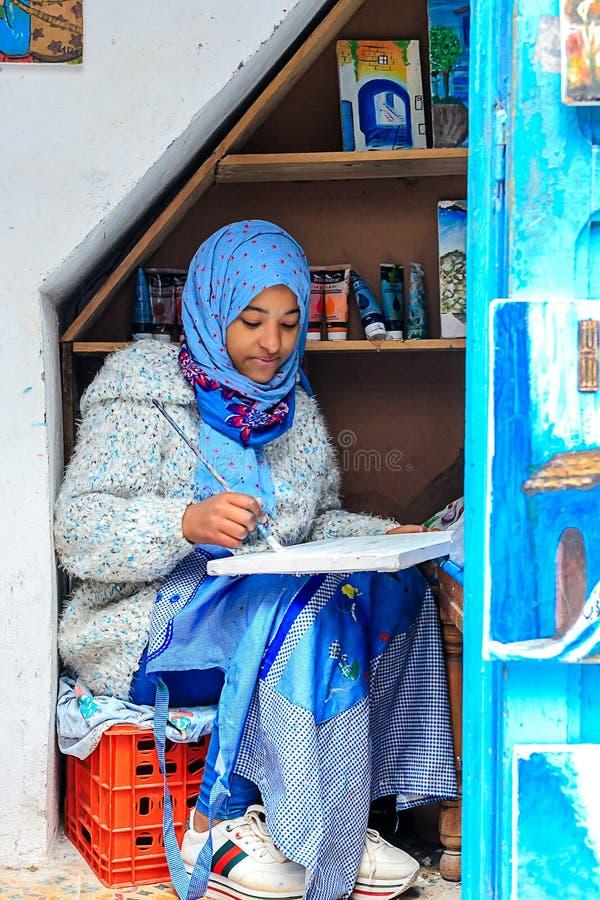 Ένα όμορφο μαροκινό κορίτσι, ένας μουσουλμάνος, καλλιτέχνης οδών χρωματίζει μια εικόνα με μια βούρτσα σε ένα μικρό εργαστήριο στοκ φωτογραφία με δικαίωμα ελεύθερης χρήσης