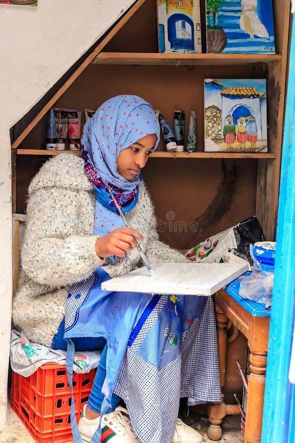 Ένα όμορφο μαροκινό κορίτσι, ένας μουσουλμάνος, καλλιτέχνης οδών χρωματίζει μια εικόνα με μια βούρτσα σε ένα μικρό εργαστήριο στοκ φωτογραφίες
