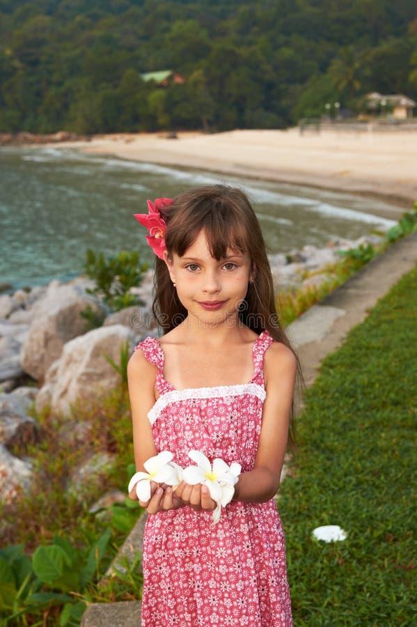 Ένα όμορφο μικρό κορίτσι με τα λουλούδια στα χέρια της στοκ εικόνα με δικαίωμα ελεύθερης χρήσης