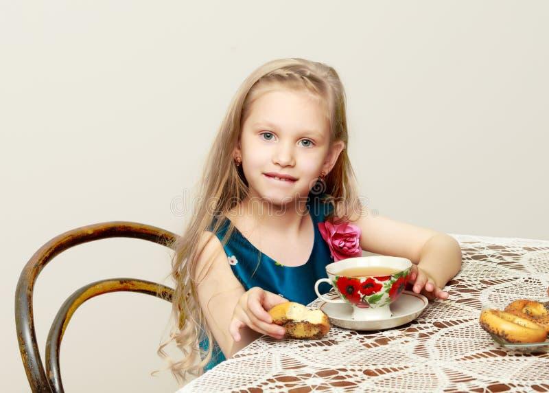 Ένα όμορφο μικρό κορίτσι με τη μακροχρόνια συνεδρίαση ξανθών μαλλιών σε έναν πίνακα στοκ εικόνα με δικαίωμα ελεύθερης χρήσης