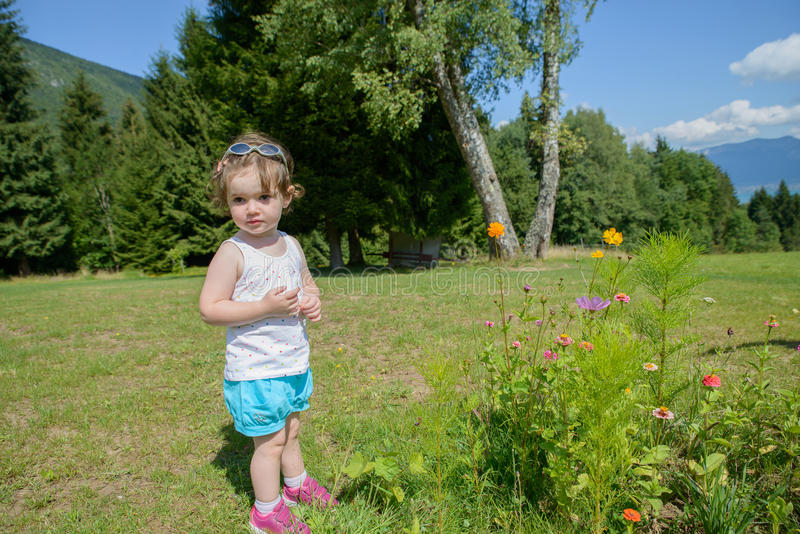 Ένα όμορφο μικρό κορίτσι που παίζει με τα λουλούδια στον κήπο στοκ φωτογραφία