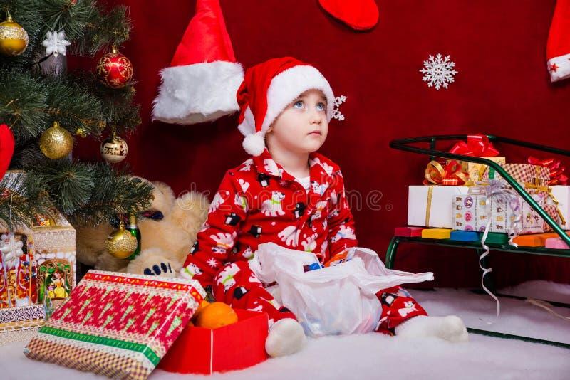 Ένα όμορφο μωρό κάθεται κοντά σε ένα χριστουγεννιάτικο δέντρο στοκ εικόνα