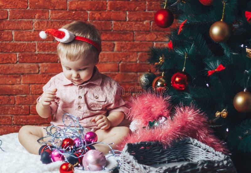 Ένα όμορφο μωρό σε ένα καπέλο santa κάθεται κοντά σε ένα χριστουγεννιάτικο δέντρο με τα παιχνίδια και τα φω'τα Χριστουγέννων στοκ φωτογραφίες