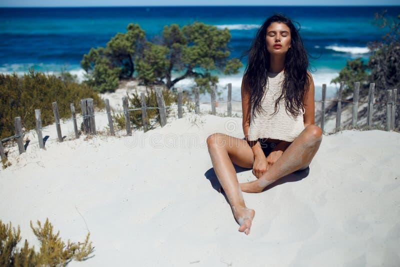 Ένα όμορφο νέο κορίτσι με τη μακριά τρίχα brunette, που εγκαθιστά στην καυτή άμμο με τις ιδιαίτερες προσοχές, στο υπόβαθρο παραλι στοκ εικόνες