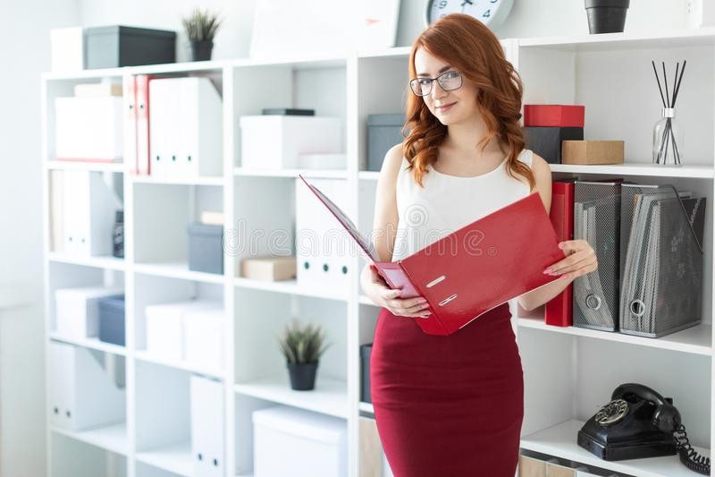 Ένα όμορφο νέο κορίτσι στέκεται κοντά σε έναν σωρό στο γραφείο και κρατά έναν φάκελλο με τα έγγραφα στα χέρια της στοκ φωτογραφία