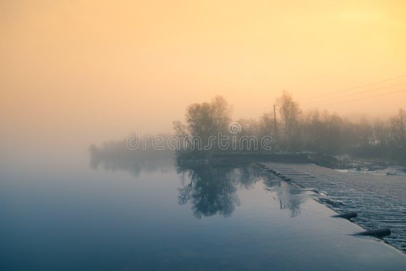 Ένα όμορφο νορβηγικό τοπίο φθινοπώρου Misty πρωί σε μια λίμνη Νερό που ρέει πέρα από το φράγμα, καταρράκτης στοκ εικόνες