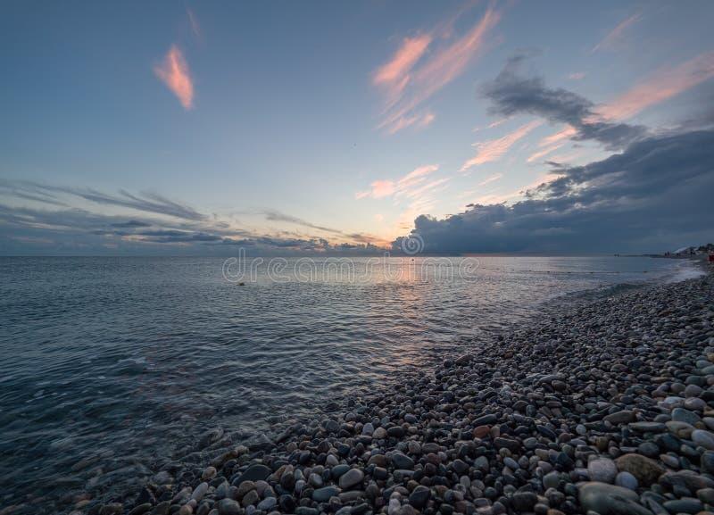 Ένα όμορφο ρόδινο ηλιοβασίλεμα σε μια παραλία χαλικιών στοκ φωτογραφία