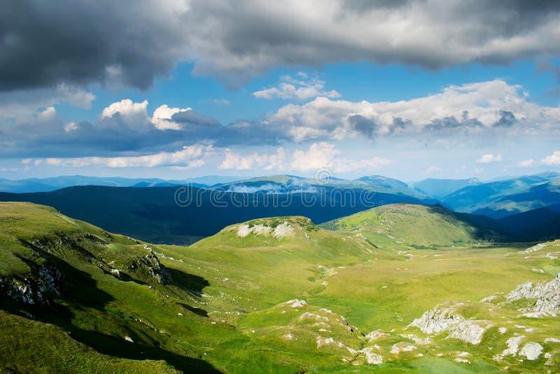 Ένα όμορφο τοπίο βουνών Ένας δραματικός, μπλε ουρανός με πολλά σύννεφα Τα ύψη των βουνών που καλύπτονται με την πράσινη χλόη και στοκ φωτογραφία με δικαίωμα ελεύθερης χρήσης
