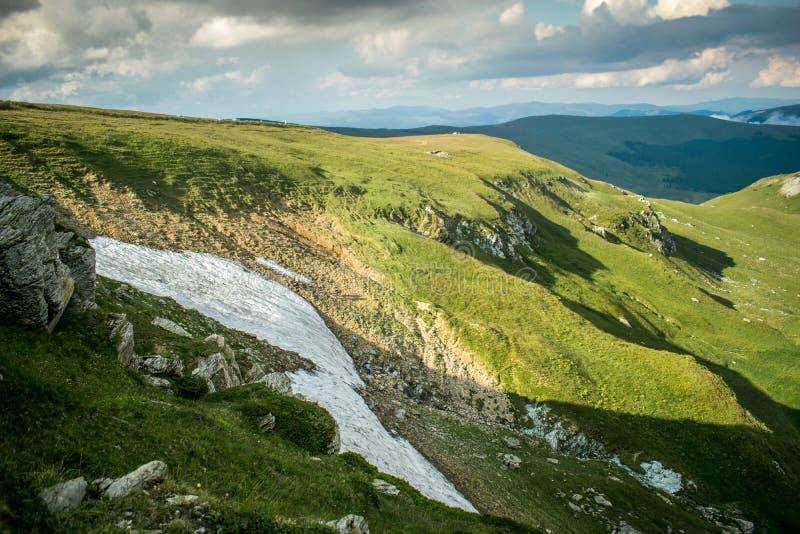 Ένα όμορφο τοπίο βουνών Τα ύψη των βουνών που καλύπτονται με τη χλόη και το χιόνι τον Ιούλιο Ένας δραματικός ουρανός στοκ φωτογραφίες