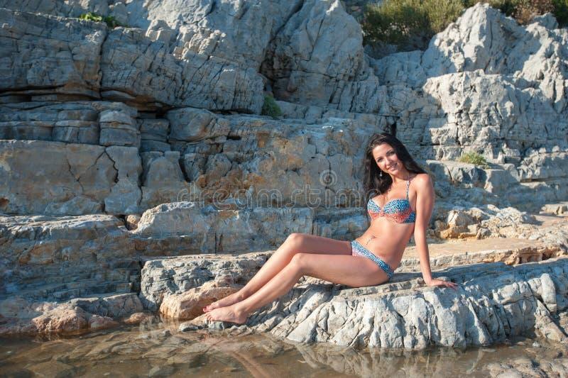 Ένα όμορφο brunette σε ένα μπικίνι κάθεται σε μια πέτρα Προκλητικό κορίτσι brunette στην τοποθέτηση μπικινιών σε μια παραλία στοκ εικόνα
