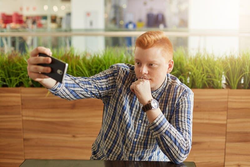 Ένα όμορφο redhead άτομο με το μοντέρνο κούρεμα έντυσε στο ελεγχμένο κομψό πουκάμισο κάνοντας selfie ενώ έχοντας ένα υπόλοιπο στο στοκ εικόνες με δικαίωμα ελεύθερης χρήσης