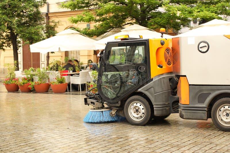 Ένα όχημα αποκομιδής απορριμμάτων οδών σκουπίζει επάνω σε ένα πεζοδρόμιο πετρών με μια ισχυρή βούρτσα στο βροχερό καιρό Διατήρηση στοκ φωτογραφία