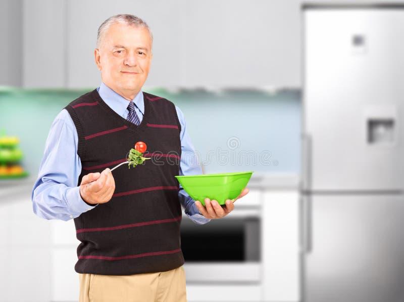 Ένα ώριμο άτομο που τρώει τη σαλάτα κατά τη διάρκεια ενός μεσημεριανού γεύματος στοκ φωτογραφία με δικαίωμα ελεύθερης χρήσης