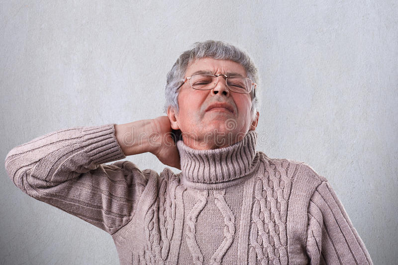Ένα ώριμο άτομο που φορούν το θερμό πουλόβερ και eyeglasses που κρατούν το χέρι του στο λαιμό που κουράζεται μετά από την εργασία στοκ φωτογραφία με δικαίωμα ελεύθερης χρήσης