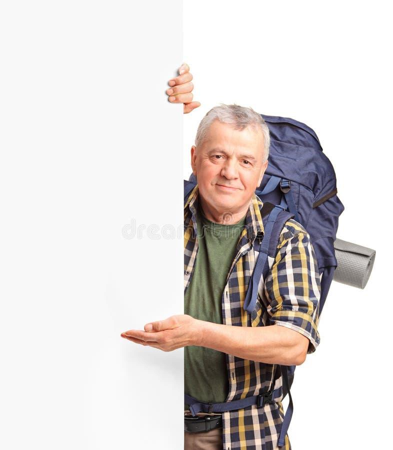 Ένα ώριμο Backpacker που σε μια λευκιά επιτροπή Στοκ Εικόνα