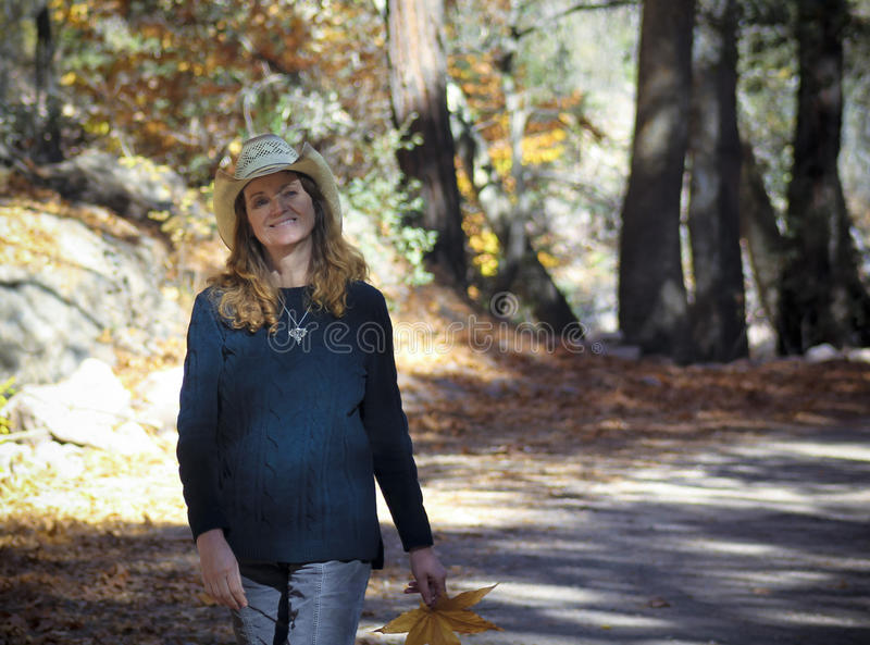 Ένα Cowgirl περπατά έναν δασικό δρόμο το φθινόπωρο στοκ φωτογραφίες