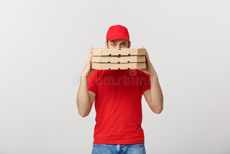 Ένα Deliveryman που κρύβεται πίσω από έναν μεγάλο σωρό των κιβωτίων πιτσών φέρνει Απομονωμένος πέρα από το γκρίζο υπόβαθρο στοκ εικόνες