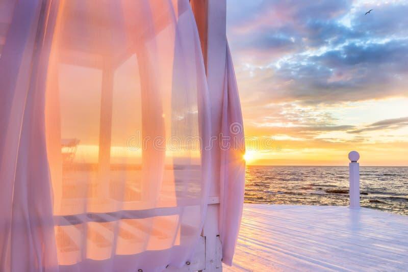 Ένα gazebo με τις εναέριες μεταδιδόμενες μέσω του ανέμου ρόδινες κουρτίνες στην ακτή στην αυγή στοκ φωτογραφία με δικαίωμα ελεύθερης χρήσης