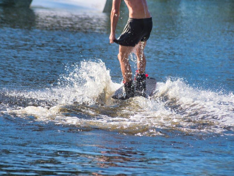 Ένα wakeboarder, ένας νεαρός άνδρας σε ένα wakeboard οδηγά στο νερό στα σορτς χωρίς μια μπλούζα στοκ φωτογραφία με δικαίωμα ελεύθερης χρήσης