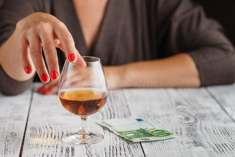 Ένα woman& x27 το χέρι του s αγγίζει ένα ποτήρι του κονιάκ στοκ εικόνες
