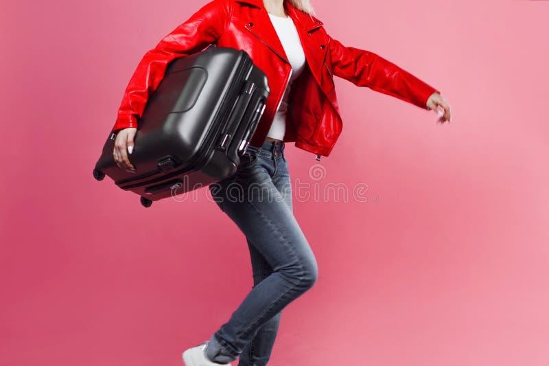 Έννοια, έτοιμη να σκοντάψει Νέα γυναίκα με τη βαλίτσα ταξιδιού αργά για την πτήση Ξανθό κορίτσι τουριστών στο ρόδινο υπόβαθρο στοκ εικόνα
