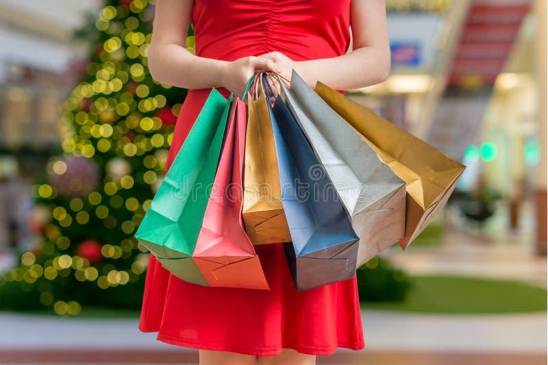 Έννοια αγορών Χριστουγέννων Η γυναίκα στέκεται με πολλές τσάντες αγορών στοκ εικόνες