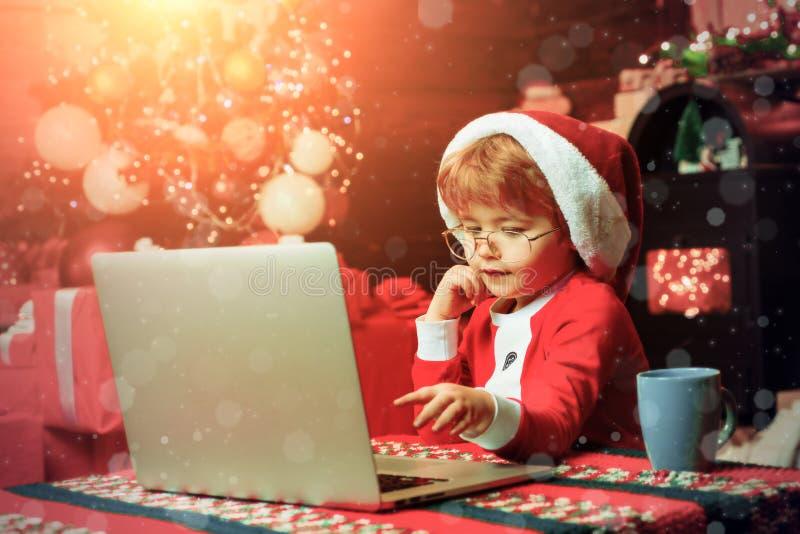 Έννοια αγορών Χριστουγέννων Υπηρεσία δώρων Santa λίγος αρωγός Έξυπνο μικρό παιδί που κάνει σερφ Διαδίκτυο Καπέλο santa μικρών παι στοκ εικόνες με δικαίωμα ελεύθερης χρήσης