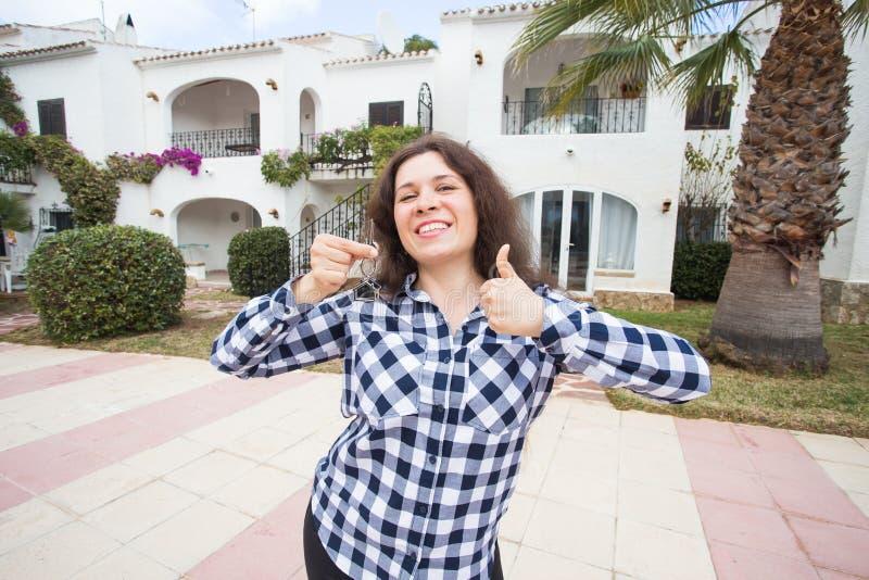 Έννοια ακίνητων περιουσιών και ιδιοκτησίας - ευτυχής νέα γυναίκα μπροστά από το νέο σπίτι με τα κλειδιά καινούργιων σπιτιών στοκ φωτογραφίες με δικαίωμα ελεύθερης χρήσης