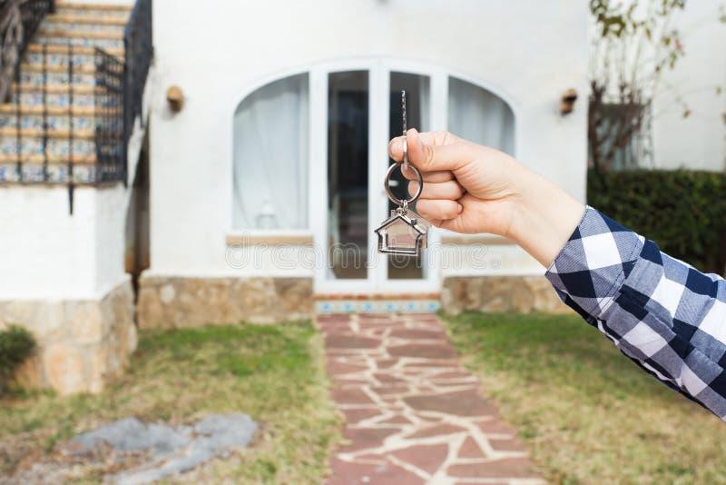 Έννοια ακίνητων περιουσιών και ιδιοκτησίας - το χέρι κρατά τα κλειδιά σπιτιών στο σπίτι που διαμορφώνεται keychain μπροστά από έν στοκ εικόνα με δικαίωμα ελεύθερης χρήσης