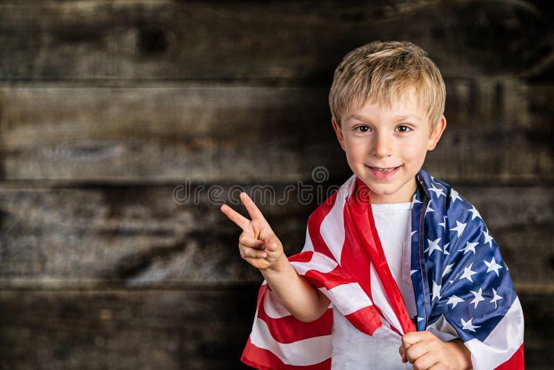 Έννοια ΑΜΕΡΙΚΑΝΙΚΟΥ εθνική εορτασμού - το νέο αγόρι στην ΑΜΕΡΙΚΑΝΙΚΗ σημαία στοκ εικόνες