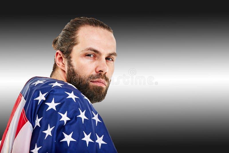 Έννοια αμερικανικού ποδοσφαίρου, πορτρέτο του φορέα αμερικανικού ποδοσφαίρου με τη αμερικανική σημαία στο μαύρο υπόβαθρο r στοκ φωτογραφία