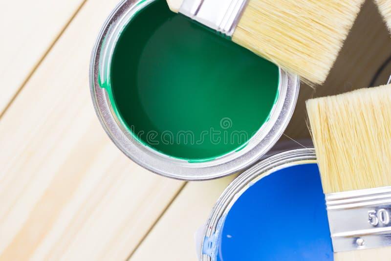 Έννοια ανακαίνισης σπιτιών, colorfull δοχεία χρωμάτων και πινέλα στο ξύλινο υπόβαθρο στοκ εικόνα