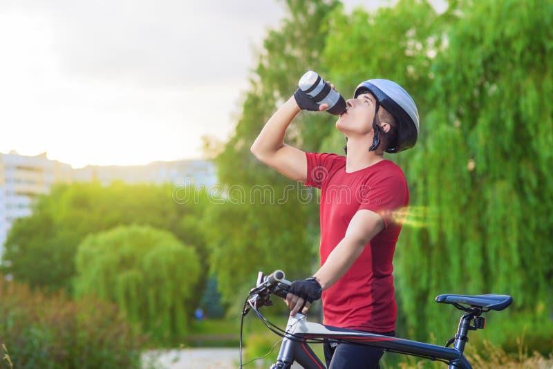 Έννοια ανακύκλωσης: Νέος καυκάσιος αρσενικός ποδηλάτης που έχει το σπάσιμο νερού στοκ εικόνες