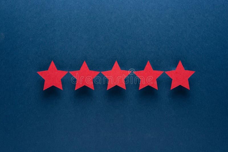 Έννοια ανατροφοδότησης Πέντε κόκκινα αστέρια εγγράφου της έγκρισης σε ένα μπλε υπόβαθρο στοκ φωτογραφίες