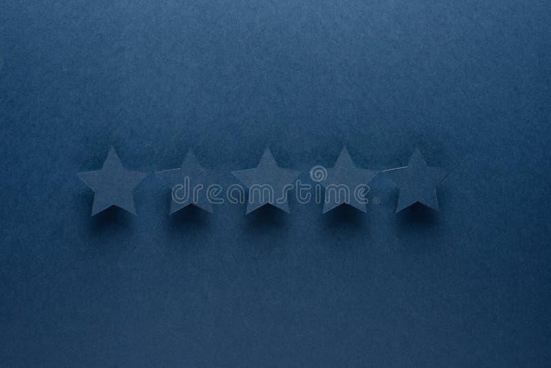 Έννοια ανατροφοδότησης Πέντε μπλε αστέρια εγγράφου της έγκρισης σε ένα μπλε υπόβαθρο στοκ φωτογραφίες